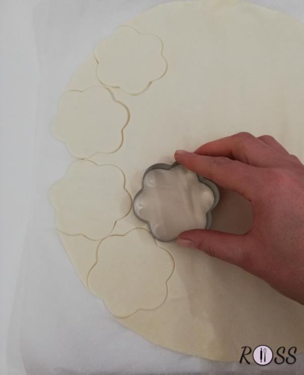 Accendete il forno, modalità ventilata, a 180°.  Srotolate la pasta sfoglia e con la formina create tanti fiori.