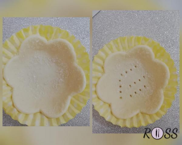 Con la pasta rivestite le pirottine ( utilizzatene 2 per ogni cestino). Con un pennello cospargete i bordi del fiore con dell'olio e cospargete con dello zucchero. Punzecchiate la base con una forchetta.