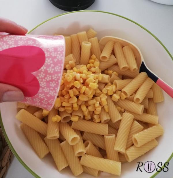 Cuocete la pasta. Appena sarà cotta, scolatela e ponetela in una ampia terrina. Iniziate aggiungendo il mais.