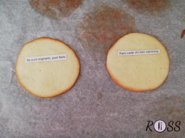 Una volta sfornati, girateli sull'altro lato e posizionate il bigliettino al centro, mentre il biscotto è ancora caldo.