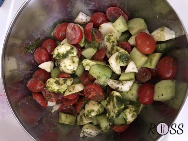 Prepara le verdure e la feta, tagliandole a dadini, amalgamandole con il pesto e le foglie di basilico