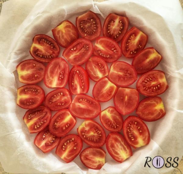 Su una teglia rotonda, rivestita con carta forno, adagia i pomodorini