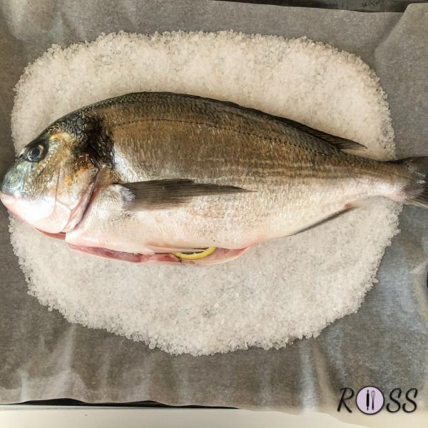 Adesso, in una teglia rivestita con carta forno, poni un kilo di sale grosso. Adagia il pesce